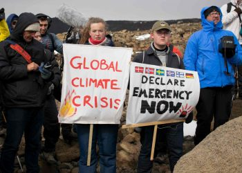 People hold up signs as a monument was unveiled at the site of Okjokull, Iceland's first glacier lost to climate change in the west of Iceland on August 18, 2019. (Photo by Jeremie RICHARD / AFP)